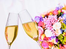 Champagne flutes with golden bubbles on wedding flowers background. Champagne flutes with golden bubbles make cheers on wedding flowers background Royalty Free Stock Photography