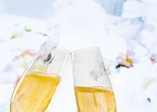 Champagne flutes with golden bubbles on wedding flowers background Stock Photography
