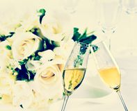 Champagne flutes with golden bubbles on wedding flowers background Stock Images