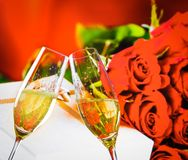 Champagne flutes with golden bubbles on wedding roses flowers background. Champagne flutes with golden bubbles make cheers on wedding roses flowers background Stock Images