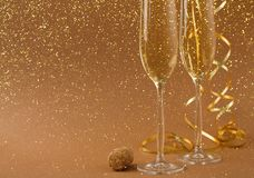 Champagne flutes on golden holiday background. Champagne flutes and bottle cork at golden holiday background with glitters and tinsel. Celebrating christmas, new Royalty Free Stock Photo