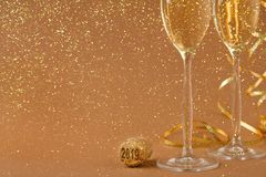 Champagne flutes on golden holiday background. Champagne flutes and bottle cork with 2019 numbers at golden holiday background with glitters and tinsel Stock Photo