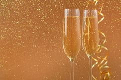 Champagne flutes on golden holiday background. Champagne flutes at golden holiday background with glitters and tinsel. Celebrating christmas, new year or Royalty Free Stock Images