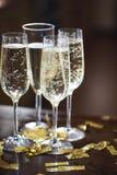 Champagne Flutes In Golden Sparkle bakgrund med guld- konfettier arkivfoton