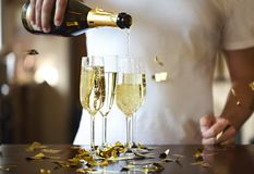 Champagne Flutes In Golden Sparkle bakgrund med guld- konfettier H?llande gnistrandevin f?r man royaltyfri bild
