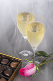 Champagne Flutes, Gourmet Chocolates, and a Pink Rose on Gray Tulle Background Stock Image