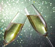 Champagne flutes on green light bokeh background Royalty Free Stock Image