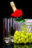 Champagne flutes in ice bucket, glasses and grape Stock Images