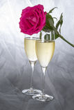 Champagne Flutes and a Pink Rose on Gray Tulle Background #1 Royalty Free Stock Photography