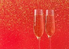 Champagne flutes on red holiday background Stock Photography