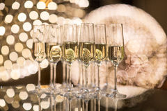 Champagne flutes on shiny, glassy background. With lovely blurred lights in the background royalty free stock images