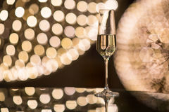Champagne flutes on shiny, glassy background. With lovely blurred lights in the background stock images