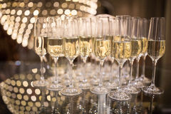 Champagne flutes on shiny, glassy background. With lovely blurred lights in the background royalty free stock photos