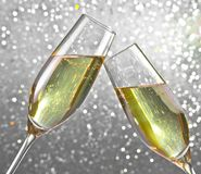 Champagne flutes on silver light bokeh background. Champagne flutes make cheers on silver light bokeh background Stock Photos