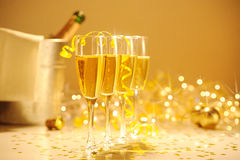Champagne flutes on table decorated with streamer and gold confe Royalty Free Stock Images