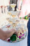 Champagne in the form of a cascade or pyramid lit light at the wedding party stock photos