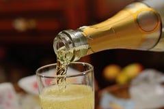 Champagne från en flaska hälls i ett exponeringsglasslut upp arkivbilder