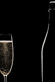 Champagne full flute and bottle. Champagne flute and bottle in black background Royalty Free Stock Photos