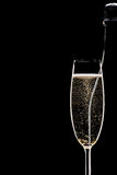 Champagne full flute and bottle. Behind on black background Royalty Free Stock Images