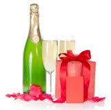 Champagne gåvaasken, kronblad av rosor och tömmer royaltyfria foton