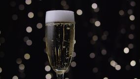 Champagne giet wit schuim door de randen van het glas uit De achtergrond van Bokeh stock video