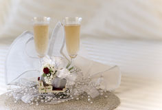 Champagne and gift. Chrystal champagne flutes filled with champagne, decorative sleigh holding small elegantly wrapped gift stock images
