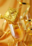 Champagne with gift. Two glasses with champagne and gift on gold background royalty free stock images