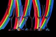 Champagne-Gläser mit Neonlicht hinten lizenzfreies stockbild