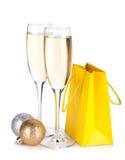 Champagne-Gläser, Weihnachtsflitter und Geschenk bauschen sich Stockfotografie