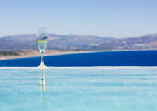 Champagne-Glas durch Swimmingpool Stockfoto