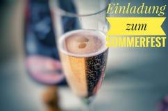 Champagne-glas met edele champagne en inschrijving in geel in Duitse Einladung zum Sommerfest, in Engelse Uitnodiging voor su royalty-vrije stock afbeelding