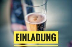 Champagne-glas met edele champagne en inschrijving in geel op Duitse Einladung, in Engelse uitnodiging royalty-vrije stock afbeeldingen