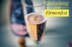 Champagne-Glas mit feinem Champagner und Aufschrift im Gelb in Deutscher Einladungs-zum Firmenfest, in der englischen Einladung a stockfotografie