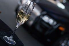 Champagne-glas op lijst met hoge eindauto op achtergrond Royalty-vrije Stock Foto's
