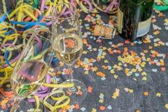 Champagne-Glas und -flasche mit Karnevalsdekoration auf einem Schiefer stockfotografie