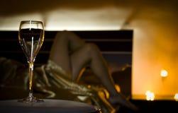 Champagne-Glas und schöne Beine verwischt im Hintergrund Stockfotografie
