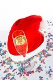 Champagne-Glas und Weihnachtshut mit Farbbändern Stockbild