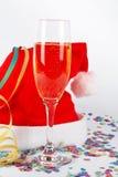Champagne-Glas und Weihnachtshut, mit Farbbändern, Confetti Stockfotografie