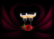 Champagne glass on black and red silk with flower Stock Image