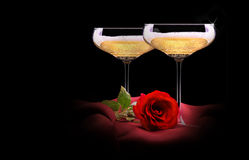 Champagne glass on black and red silk with flower Stock Photos