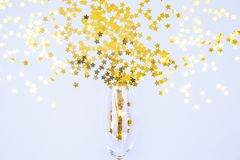 Champagne glass bursting with sprinkles on blue background. Holiday, party and celebration concept stock photos