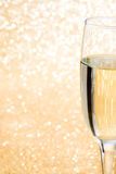 Champagne glass cup on brilliant golden background Stock Photos