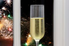 Champagne glass in front of a window on New Year`s Eve with fireworks royalty free stock photo