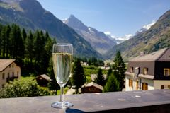 Champagne glass on mountain village background. Glass of champagne on Swiss mountain village Zinal background in summer. Val d`Anniviers, Valais, Switzerland royalty free stock photo