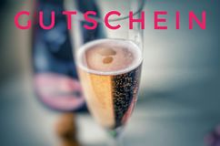 Champagne glass with noble champagne and inscription in pink on german Gutschein, in english coupon, voucher, gift card. New letters Stock Photography