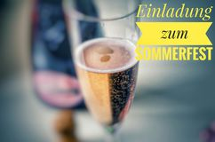 Champagne glass with noble champagne and inscription in yellow in german Einladung zum Sommerfest, in English Invitation to the su royalty free stock image