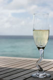A champagne glass by the ocean Royalty Free Stock Photo
