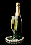 Champagne with a glass and a pearl necklace Stock Images