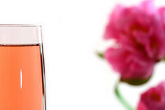 Champagne. A glass of champagne with a pink flower in the background Royalty Free Stock Image