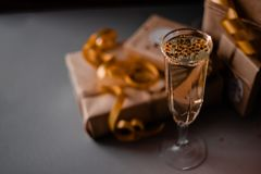 Champagne Glass Presents Decorations Background. Golden bonnets, standing on a dark table stock image